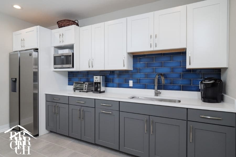 Commercial Office Renovation Staff Kitchen with Blue Backsplash and Beautiful Grey Cabinet with White Cabinet Accepts | Robinson Renovation and Custom Homes